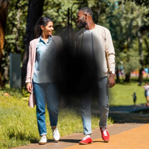 What Vision Loss Looks Like With One Of The Major Eye Diseases - Black Blurry Dot Over Image Of Couple Walking Outside